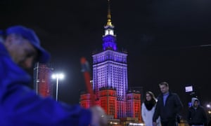People walk in front of the Palace of Culture in Warsaw, Poland.