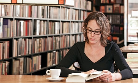 A woman reading in a bookstore.