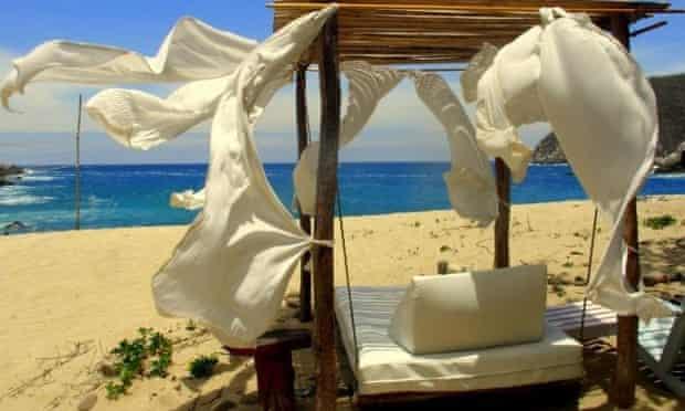 Beach lounger on the sand with a view of the sea at Bahia de La Luna, Pochutla, Oaxaca, Mexico