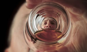 Man drinking beer, viewed from the bottom of the glass