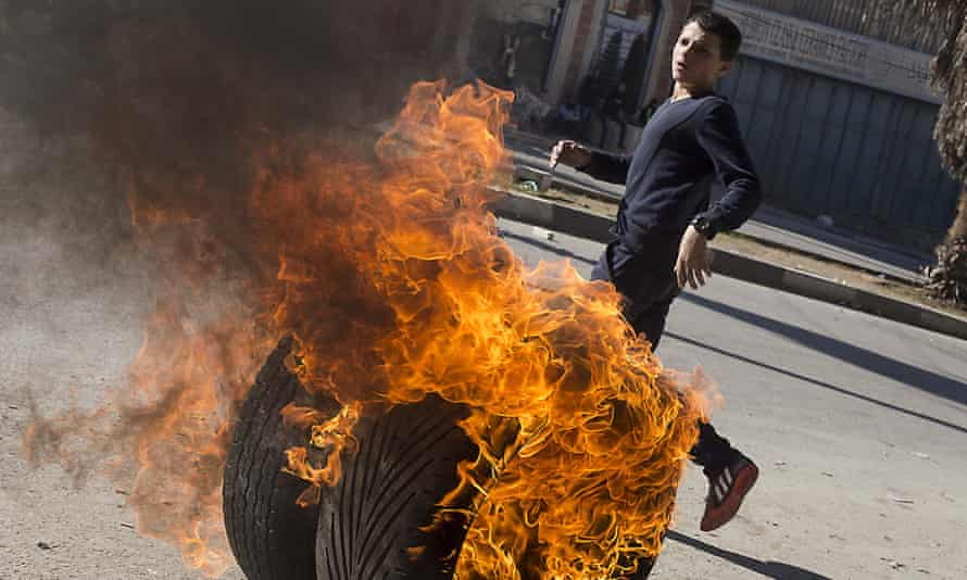 A Palestinian teenager in the flashpoint city of Hebron sets a tyre alight during a clash with Israeli security forces amid violence the Israeli military predicts will continue.