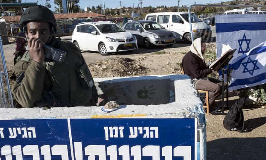 An israeli soldier guards a bus stop on the occupied West Bank while a yeshiva student prays behind him at the spot where a young Israeli woman was stabbed to death by a Palestinian assailant on Sunday.