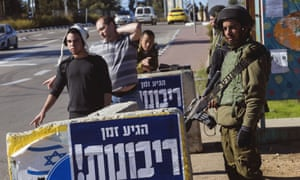 An Israeli soldier guards hitch hikers at the Gush Etzion junction in the occupied West Bank.