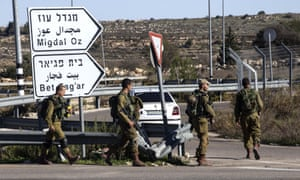 Israeli soldiers patrol the roundabout at the Gush Etzion junction situated on the main road south to Hebron.