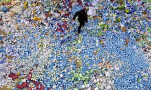 A Chinese policeman walking across a pile of fake medicines seized in Beijing.