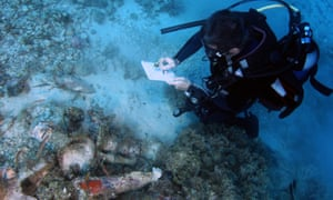 An underwater archaeologist takes notes on ancient jars found in a shipwreck.
