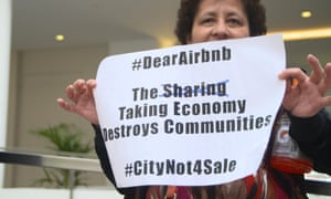 Campaigner and Causa Justa member Bilda Linares holds a banner at the protest inside Airbnb's head office