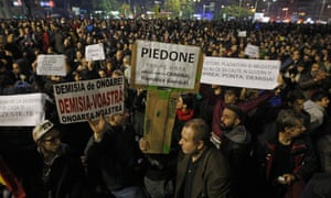 Romanians hold placards calling for the resignations of mayor Cristian Popescu Piedone, minister Gabriel Oprea and prime minister Victor Ponta.