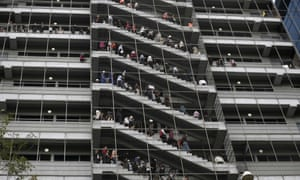 Workers stand at the emergency stairs in an office building during an earthquake drill in Mexico City.