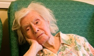 older woman in armchair looking fed up