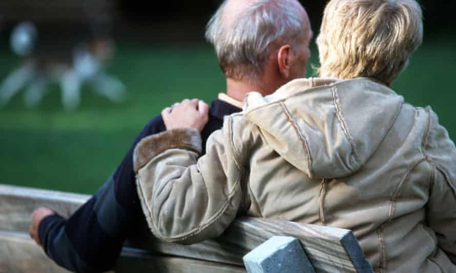 Couple sit on park bench