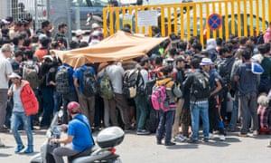 Hundreds of refugees queue outside the gate of the port in Mytilene on Lesbos.