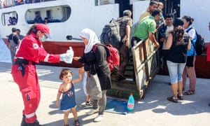 Red Cross volunteers help refugees at the port of Sitia, Crete.