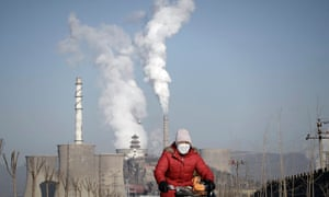 A woman wearing a mask rides past smoking chimneys and cooling towers of a steel plant in Beijing