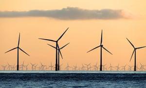 Wind turbines seen from a beach.