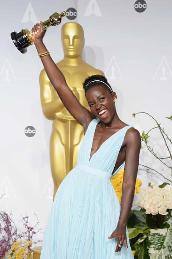 Lupita Nyong'o holding her Oscar