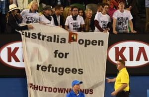 Protestors unfurl a banner.