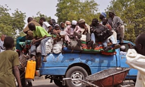 Villagers crowd on to a small lorry to flee violence near Maiduguri, Nigeria