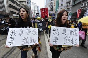 Demonstrators hold banners calling for universal suffrage.