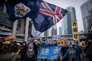 A protester waves a Hong Kong colonial flag as he marches.