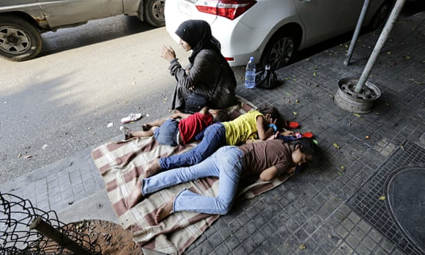 A Syrian woman sits next to her children on a street sidewalk