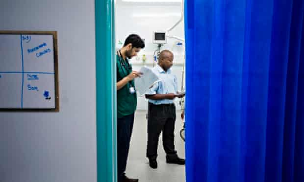 Members of a mental health team talk to a patient in A&E