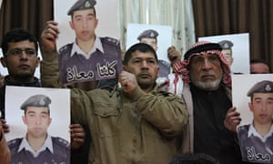 Relatives of Isis captive Muath al-Kasasbeh at a rally in Karak. The words on the portrait read 'We