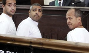 Al-Jazeera English producer Baher Mohamed, left, Canadian-Egyptian acting Cairo bureau chief Mohammed Fahmy, center, and correspondent Peter Greste, right, appear in court along with several other defendants during their trial on terror charges, in Cairo, Egypt.