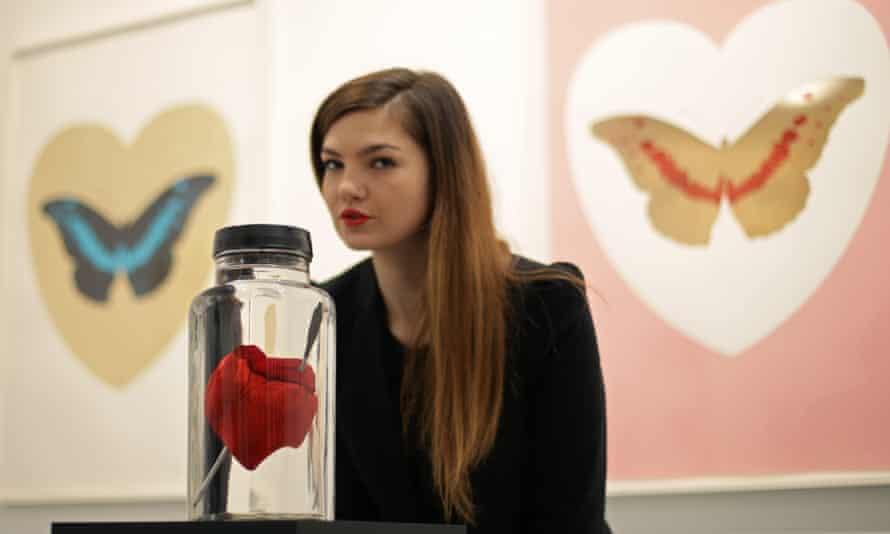 Gallery assistant Rachel Hunt with the piece Love Struck – a resin cast of a pig's heart with a steel crossbow bolt through it.