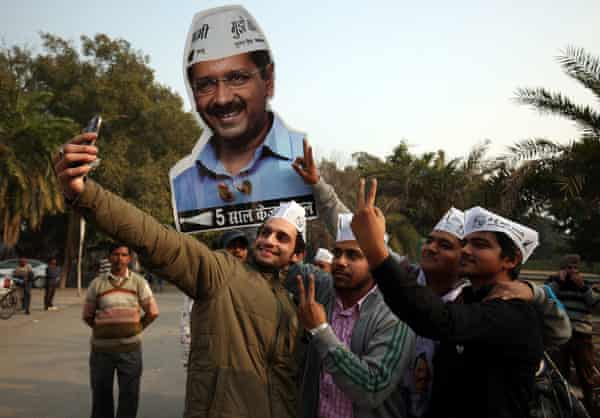 AAP supporters take a selfie with Arvind Kejriwal's picture in the background.