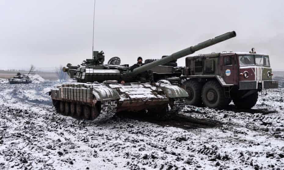Ukrainian servicemen ride in a tank past a towing truck outside Debaltseve, eastern Ukraine, where fierce fighting has been going on.