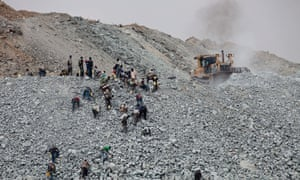 A bulldozer moves rubble as villagers search for tiny flecks of gold contained in discarded waste rock from the North Mara mine in the district of Nyangoto, Tanzania, on Saturday, July 31, 2010. Barrick Gold Corp.'s North Mara mine near the Tanzanian border with Kenya disgorges millions of pounds of waste rock each week, piled high around communities where almost half the people live on less than 33 cents a day.