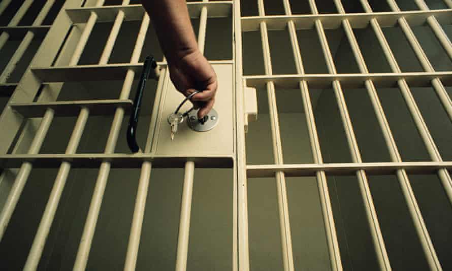 A man locking/unlocking a prison cell door