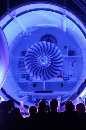 Visitors stand in front of the illuminated interior of a vacuum chamber for engine tests at a Rolls-Royce test centre.
