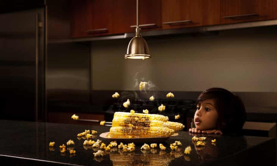 Boy (3-4) watching corn become popcorn under light