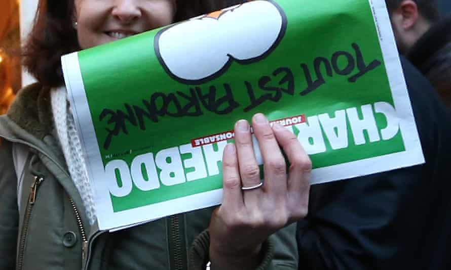 A woman holds up a copy of Charlie Hebdo magazine outside a French bookstore in London, England.