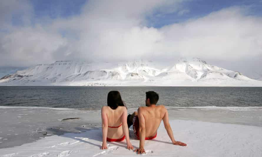 Climate activists Lesley Butler and Rob Bell (R) sunbathe on the edge of a frozen fjord in the Norwegian Arctic town of Longyearbyen in this April 25, 2007 file photo. REUTERS/Francois Lenoir/Files   (NORWAY):rel:d:bm:PM1E4AO195R01