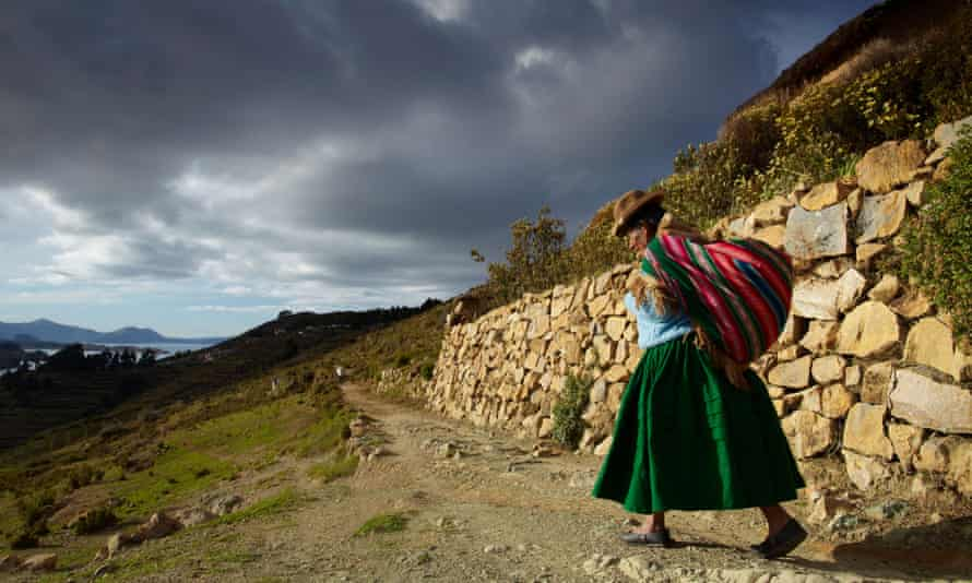 A woman with load on her back, Isla del Sol, Lake Titicaca, Bolivia.