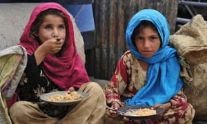 Afghan children eat a meal of rice in Jalalabad
