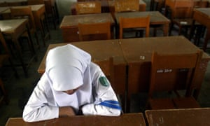 A Muslim high-school girl sits in a classroom. A local Indonesian MP had proposed that all girls have a virginity test in order to graduate from school.