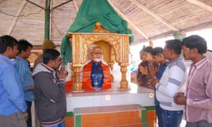 Indian villagers assemble and pray by an idol of Modi at a temple erected in his honour.