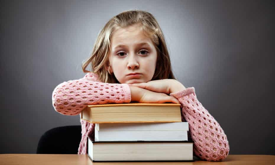 Young girl leaning on stack of books