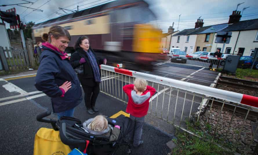 A level crossing at Cardinalls Road, Stowmarket, Suffolk.Rosie Carter (blue scarf) and Kym Halladay with Georgia (in buggy) and Harry age 4.Photograph: Graham Turner. trainstransportrailwaycrossing