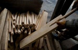 A worker fits handle into a spliced cricket bat