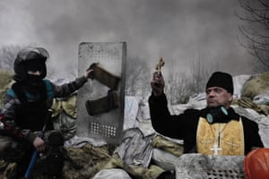 World Press Photo, the 2nd prize in the Spot News Stories category  by Jerome Sessini, France, Magnum Photos for De Standaard shows an Orthodox priest blessing the protesters on a barricade in Kiev, Ukraine