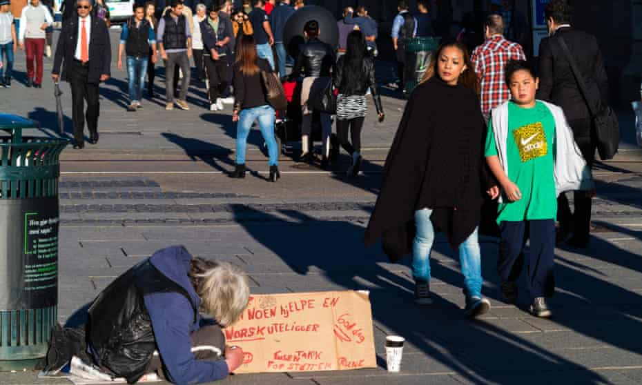 People walk past a man begging on a street in central Oslo.