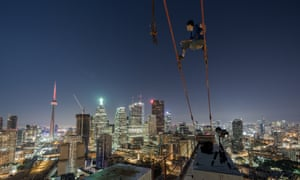 A shot of rooftopping photographer Tom Ryaboi above the streets Toronto. Ryaboi was arrested earlier this month.