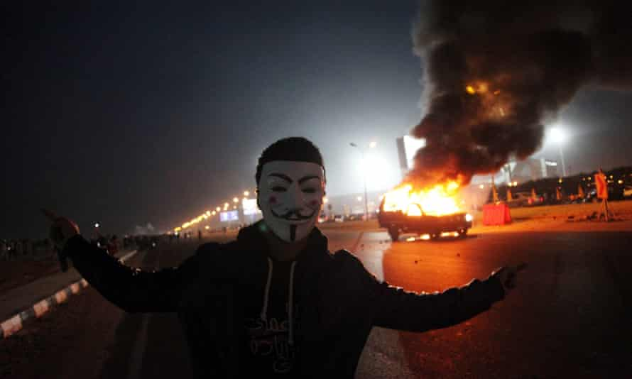 A Zamalek supporter wearing a Guy Fawkes mask near a burning police car outside the stadium in Cairo.