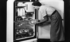 Woman loading food into a fridge in the 1950s