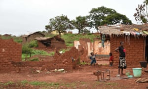 Children stand outside houses damaged by former Seleka fighters in the village of Gaga, near Yaloke.